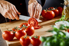 Close Up On Man Slicing Up Small Tomatoes
