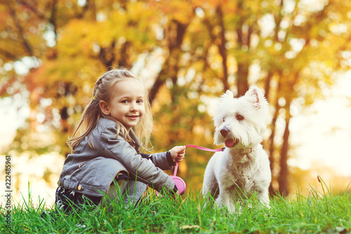 Little girl with dog in autumn park Wallpaper Mural