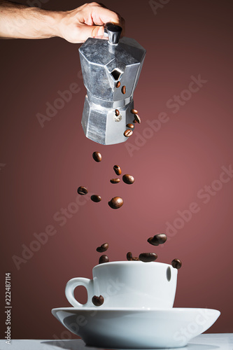 Coffee pot pouring roasted coffee beans into the cup