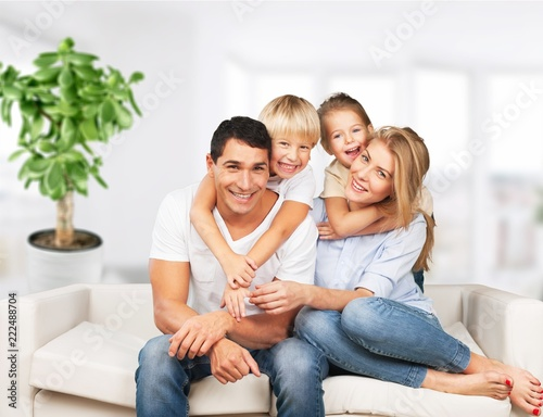 Beautiful smiling family sitting at sofa on room background