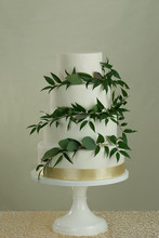 4 Tier Wedding Cake With Gold Ribbon And Green Leafy Vine Decoration.