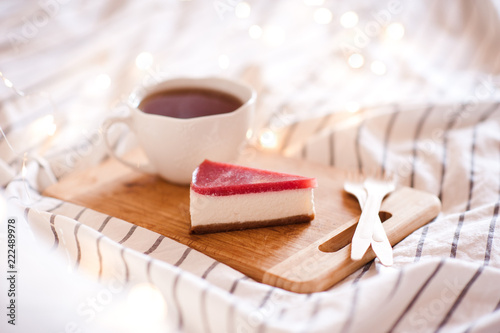 Photographie  Cup of tea with cheesecake on wooden tray in bed. Good morning.