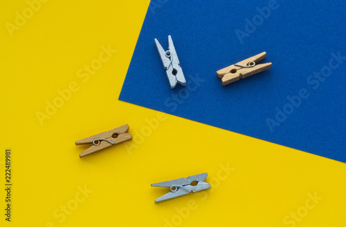 Fotografie, Obraz  Small clothespins on a yellow blue background