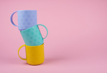 Stack Of Blue, Green And Yellow Cups On A Pastel Pink Background (minimalism Concept), Copy Space On The Right For Your Text