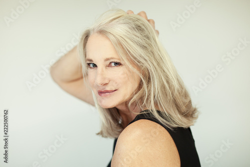 Fototapeta stunning beautiful and self confident best aged woman with grey hair smiling into camera, portrait with white background obraz
