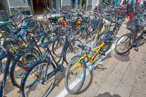 Photo  Copenhagen, Denmark-August 1, 2018: Bicycles parked on a busy historic city stre