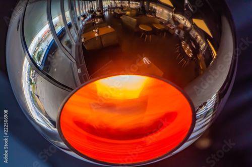 Fotografiet  A burning mirror spherical lamp with a reflection of a cafe is on a blue and vio