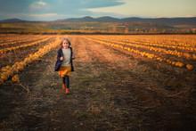 Happy Girl In Dark Blue Coat Running On The Pumpkin Field