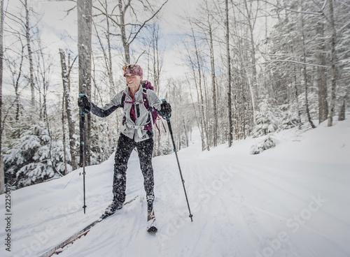 Keuken foto achterwand Wintersporten Woman skiing in forest in winter