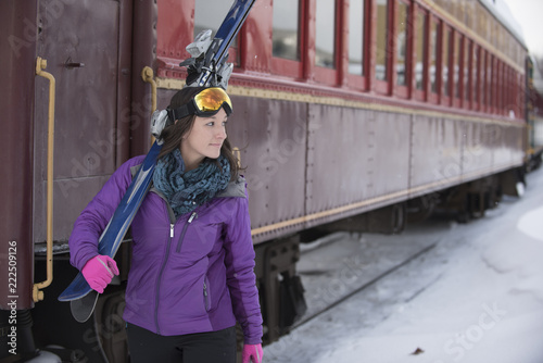 Woman carrying skis outdoors in winter