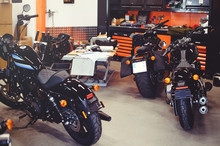 Many Motorcycles On The Floor With Workshop Tools, A Modern Garage, Storage And Repair. This Bike Will Be Perfect. Repairing A Motorcycle In A Repair Shop