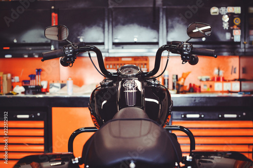 motorcycles on the floor with workshop tools, a modern garage, storage and repair. This bike will be perfect. repairing a motorcycle in a repair shop