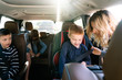 A mother helping her son to fasten seatbelt in a car