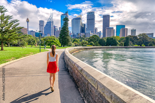 fototapeta na ścianę Sydney city girl tourist walking in urban park with skyscrapers skyline in the background. Australia travel vacation in the summer. Australian people lifestyle living.