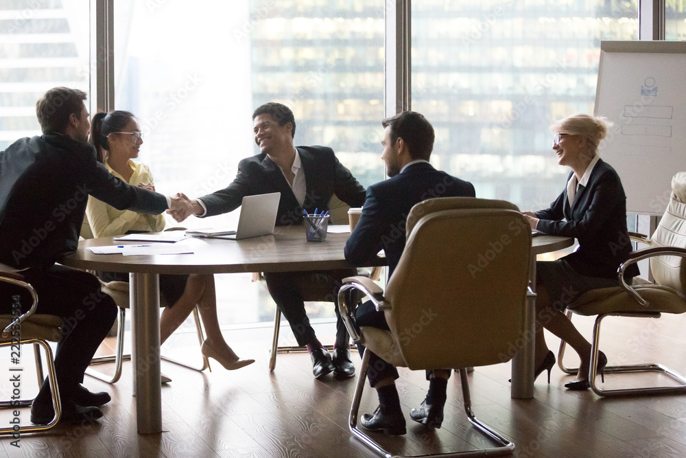 Fototapeta Smiling multiracial business people sitting at meeting in conference room and handshake. Asian, African american professional workers. Good work results, reach agreement and signing contract concept