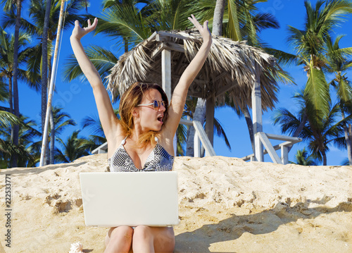 Fotografia  Girl with laptop on tropical beach. remote working concept