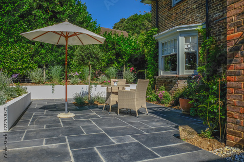 Spoed Fotobehang Tuin Table and chairs on the patio in an English country garden