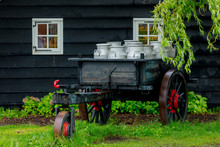 Old Traditional Dutch Cans In A Carriage In Village. Holland, Netherlands