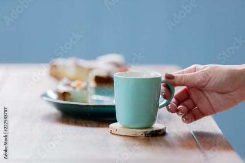 Foto op Aluminium Aromatische Female hand holding cup near pate with eaten cake and spoon on wooden table. Side view
