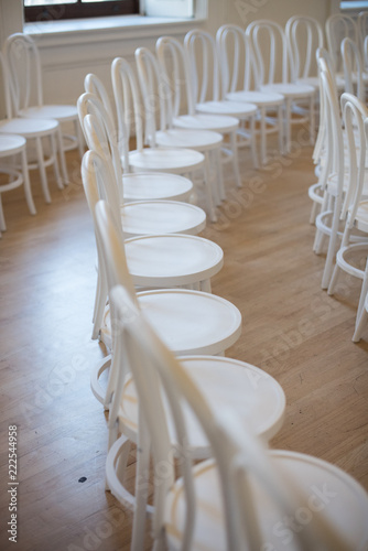 White chairs in rows arranged for a wedding ceremony