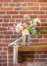 Bride's Bouquet With Dahlias On A Brick Wall Background