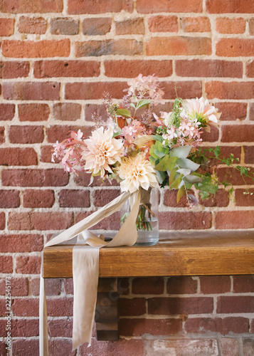 Fotobehang Wand Bride's bouquet with dahlias on a brick wall background