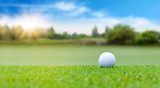 White Golf ball on green course to be shot on blurred beautiful landscape of golf course in bright day time with copy space. Sport, Recreation, Relax in holiday concept