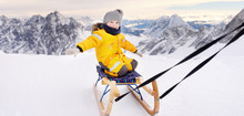 Cute Caucasian Little Boy Sledding In Alps Mountains