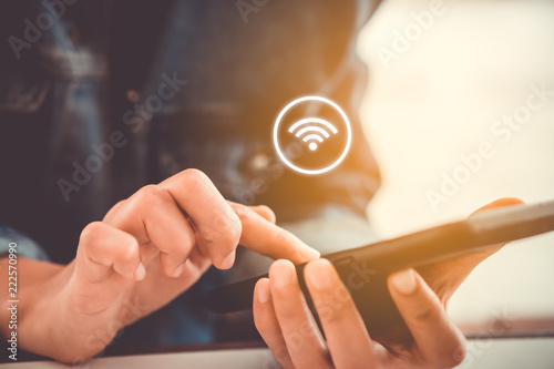 Fotografía  Woman hand using smartphone with wifi icon in cafe shop background