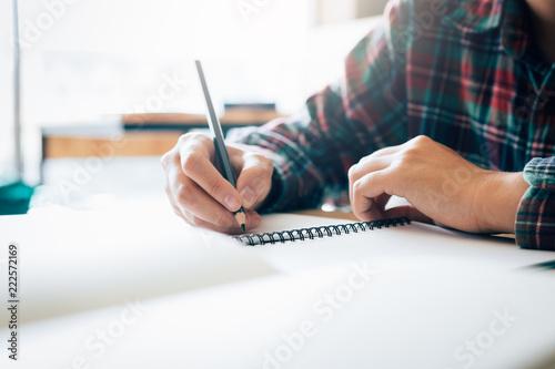 Fototapeta Teenage student works on homework in his room and writing in notebook. obraz na płótnie
