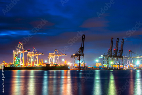 Forklift handling moving freight cargo containers on industrial working site at night