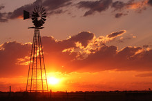 Beautiful Silhouette Off A Windmill During A Pretty Sunset On A Vast Open Plain.