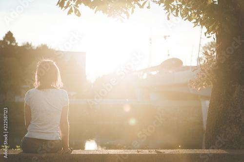 Fotografía Junge Frau sitzt in urbaner Gegend auf Mauer und blickt dem Sonnenuntergang entg