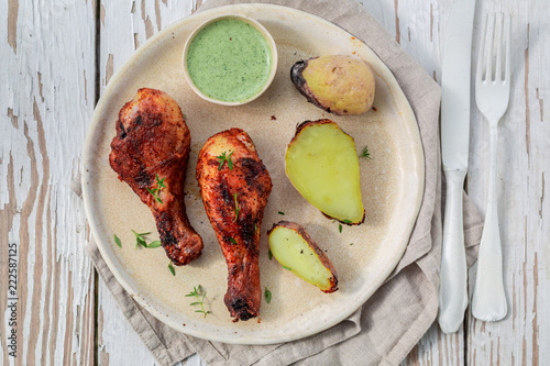 Spicy roasted chicken on rustic white table