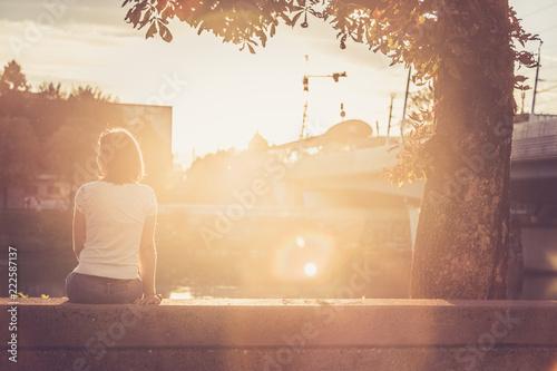 Fotografie, Obraz  Junge Frau sitzt in urbaner Gegend auf Mauer und blickt dem Sonnenuntergang entg