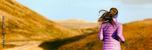 Running woman in autumn foliage background. Athlete runner on trail run outdoors panoramic banner. Active person jogging in down jacket from behind.