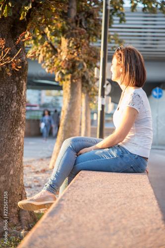 Junge Frau sitzt in urbaner Gegend auf Mauer und blickt dem Sonnenuntergang entg Canvas Print