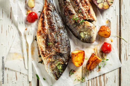 Homemade potatoes and seabream with herbs and tomatoes