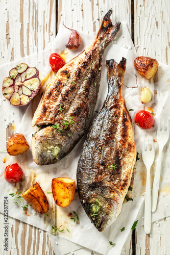 Grilled seabream and potatoes with herbs and tomatoes
