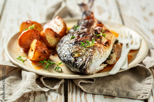 Homemade potatoes and seabream with cherry tomatoes and thyme