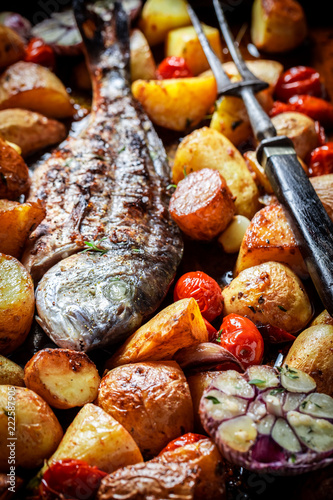 Roasted seabream and potatoes with herbs and tomatoes