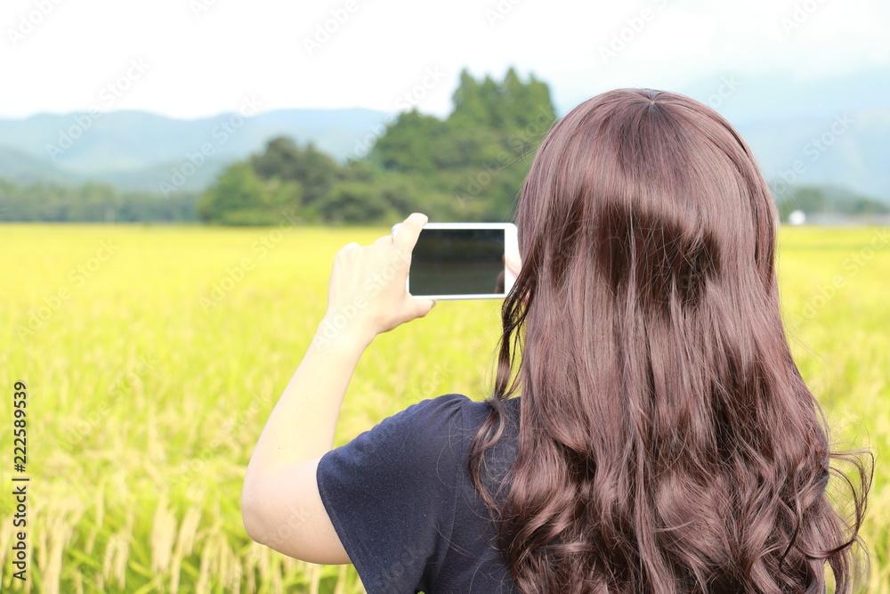 Fototapeta スマートホンで写真を撮る女性 田舎 ひとり旅 イメージ