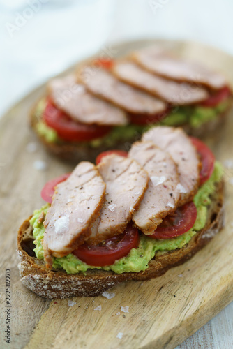 Pork tenderloin sandwich with mashed avocado, tomatoes and maldon salt. Served on a wooden cutting board, high resolution.