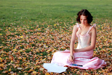 Fine Emotional Brunette Paint On Paper, Sitting On Autumn Leaves And Grass. Copy Space. Yonge Girl In Vintage Pink Pastel With Live Expressions On Beautiful Country And Old Background.