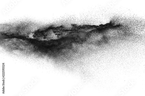 obraz dibond Black particles splattered on white background. Black powder dust splashing.