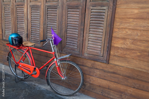 Staande foto Fiets Red bike and wooden cover.