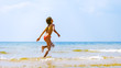 Summer fun beach woman splashing water. Panorama landscape of tropical ocean on travel holiday. Bikini girl running in freedom and joy with hands up enjoying the sun.