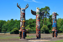Three Colorful Wooden Totem Poles On Green Trees And Blue Sky Background Outdoors In Park.