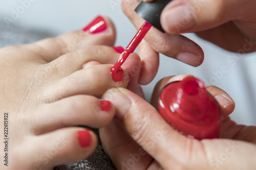 Fotobehang Pedicure The master covers the customer's nails with varnish. Hands in gloves cares about a woman's foot nails. Pedicure, manicure beauty salon concept. Nail varnishing in red color.
