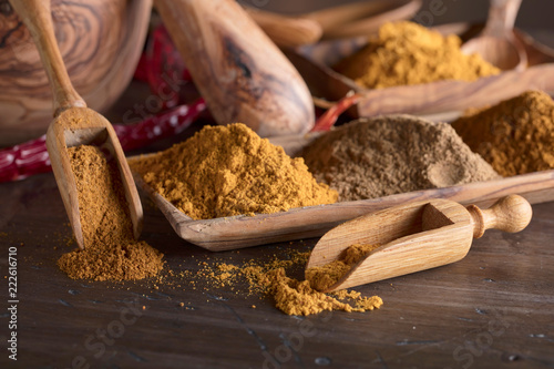 Foto op Aluminium Aromatische Various Indian spices with wooden spoons on a wooden table.